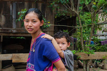 penury: BAAN PONGSAYAN ,MAE CHAEM,CHIANGMAI,THAILAND - MAY 28 ; Unidentified karen ethnic woman with her child pose for photo on May 28,2014 in Bann Pongsayan,Mae Chaem Chiangmai,Thailand