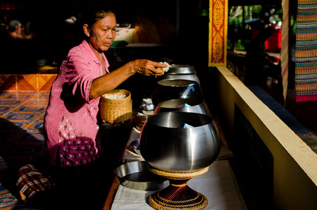 UDONTHANI , THAILAND - JULY 6   The old woman puts food offerings in a Buddhist monk s alms bowl at Wat Pa Banmuang on July 6, 2014 in Udonthani , Thailand