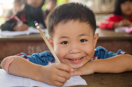 kap: KAP CHOENG,SURIN,THAILAND-JULY 20  Unidentified happy Khmer kid is trying to write khmer character in classroom at Chong Jom market  Thai-cambodia border  on July 20,2014 in KapChoeng, Surin,Thailand  Editorial