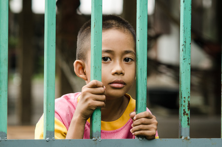 dejected: Boy behind iron bars Stock Photo