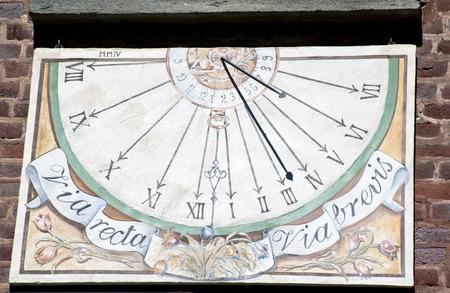 reloj de sol: el reloj de sol en la pared de ladrillo rojo. Foto de archivo