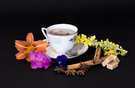 purifying: cup of hot herbal tea, surrounded by flowers and spices