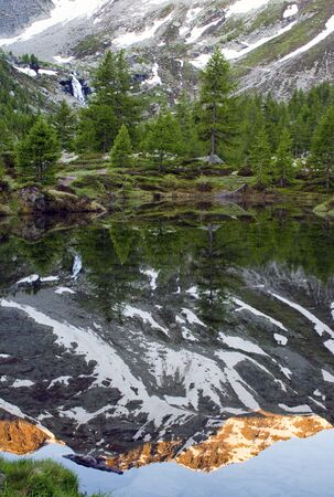 portage: beautiful reflections on the lake Arpy in the Aosta valley. Stock Photo