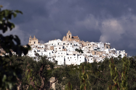 view of the white city of Ostuni between the sun and rain.