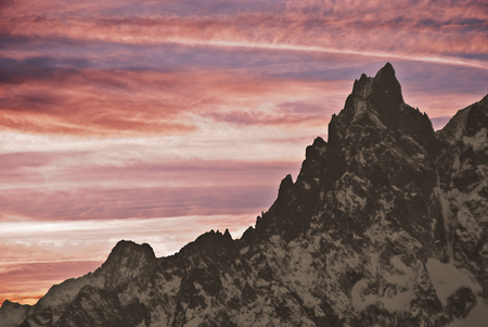 noire: clouds colored by the setting sun behind Aiguille noire. Stock Photo