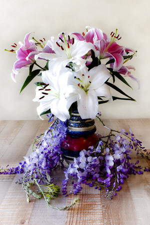 natures: The vase with lily flowers and wisteria. Stock Photo