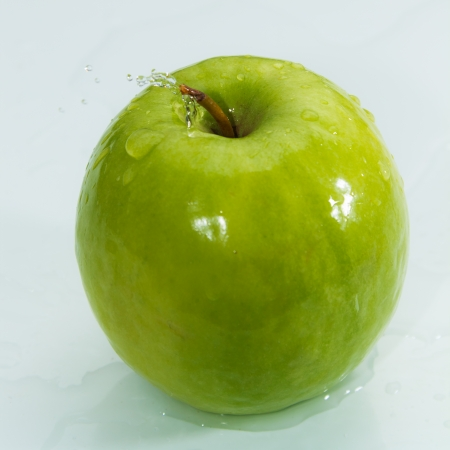 Green apple splashing into water   photo