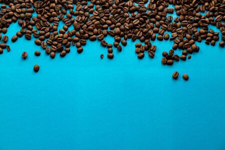 Roasted coffee beans background texture isolated on a blue background with copy space for text, close-up