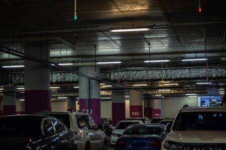 Modern underground Parking in the shopping center is full of cars. Industrial urban interior.