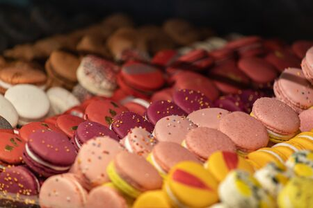 Almond cake macaron with a viscous middle and crispy shell is one of the most fashionable cakes of modern France. Multi-colored macarons lie in rows. Homemade bakery. Stok Fotoğraf