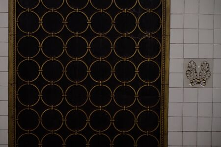 Old design element of the wall. Lattice with copper rings on the tiled wall and near the bas-relief in the form of small oak leaves. Moscow metro, Belorusskaya station. Banque d'images - 131955746