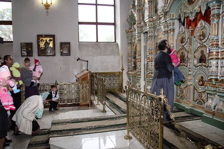 Moscow region, Russia, 08.29.2018. The interior of the wooden village Church. The Holy Orthodox rite of the sacrament of baptism newborn baby in a Christian Church.