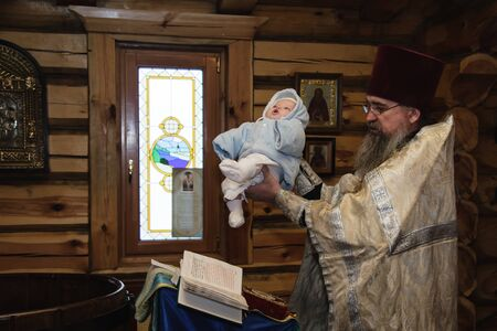 Moscow region, Russia, 01.22.2019. The interior of the wooden village Church. The Holy Orthodox rite of the sacrament of baptism newborn baby in a Christian Church.