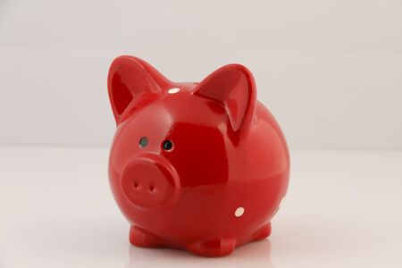 Red piggy bank filled with coins isolated on white background with clipping path Stock fotó