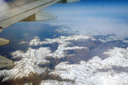 Top view of the ground from the plane. Mountain peaks of the Alps, covered with snow, among the clouds. Soft focus. 스톡 콘텐츠