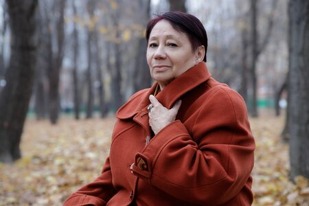 An elderly woman in a bright terracotta coat sits thoughtfully in an autumn Park Archivio Fotografico - 134806927