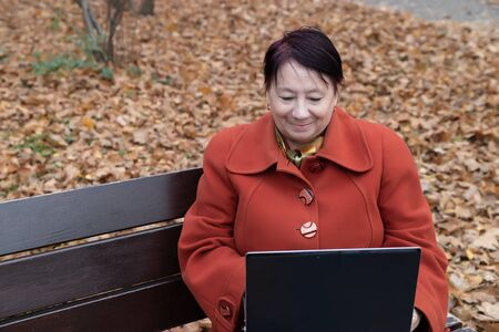 An elderly woman in a bright terracotta coat sits thoughtfully in an autumn Park Archivio Fotografico - 134806929