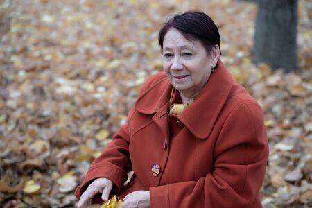 An elderly woman in a bright terracotta coat smiles sitting in an autumn Park Archivio Fotografico - 134806931
