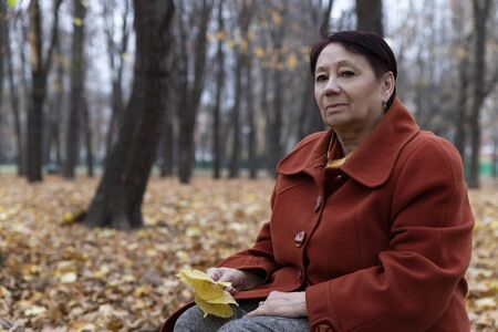 An elderly woman in a bright terracotta coat sits thoughtfully in an autumn Park Archivio Fotografico - 134806937