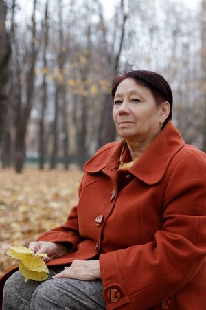 An elderly woman in a bright terracotta coat sits thoughtfully in an autumn Park Archivio Fotografico - 134806938