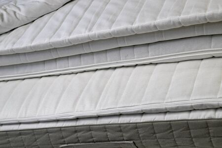 Folded white new bed mattresses filmed close-up