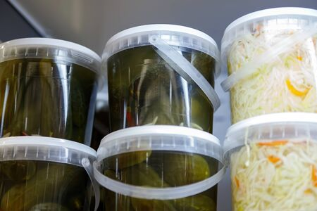 Canned, marinated fermented and pickled vegetables in plastic jars. Sauerkraut, pickles, pickled ginger in the grocery store. Banco de Imagens