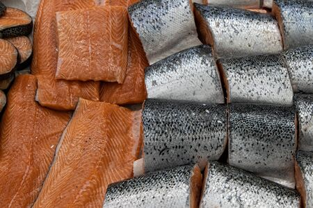 Different types of fresh fish on ice in supermarket, top view. Close up fresh fish on ice bucket or frozen fish in grocery store use for raw food background