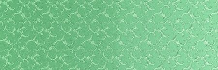 Embossed floral pattern on green paper. Textured paper with copy space. Light green, the color of fresh grass, paper surface, texture closeup.