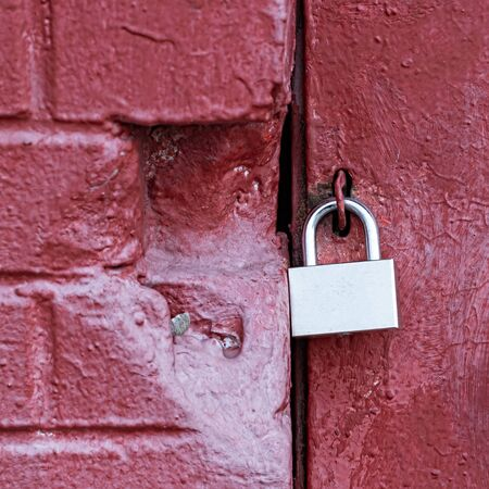 A silver padlock locks the old doors securely. Close- up view. Red brick wall. Copy space for your design Banco de Imagens