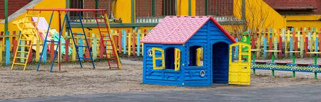 An empty Playground in a kindergarten on a Sunny spring day. Blue plastic house for fun children's outdoor games in a closed safe area.