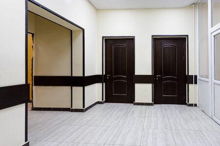 Un couloir vide dans un immeuble de bureaux moderne. Un hall aux murs clairs et aux portes marron.