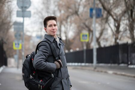 A young free handsome fashion guy dressed in a coat goes out with a backpack from home to the street to go on a trip or to study, urban style Banque d'images - 144159696