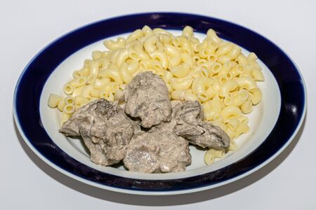Chicken liver stewed in sour cream and a side dish of pasta in a bowl on a white background, close-up. healthy food, menu concept background