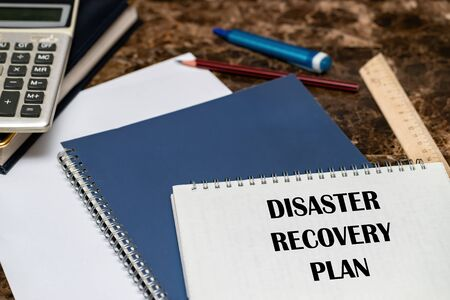 The text of the Disaster Recovery Plan is written on a white sheet lying on the office Desk. Фото со стока - 147174748