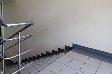 The concept of the interior of an urban building. Photo of a staircase with metal railing between floors.