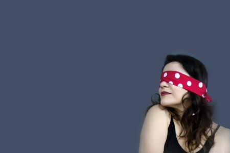 Portrait of a beautiful, fashionable middle-aged woman with long dark hair and a red blindfold covering her eyes, posing against a dark gray background. Free space to copy your design.