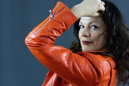 Portrait of a beautiful fashionable middle-aged woman in a bright orange leather jacket, posing on a dark gray background Banque d'images