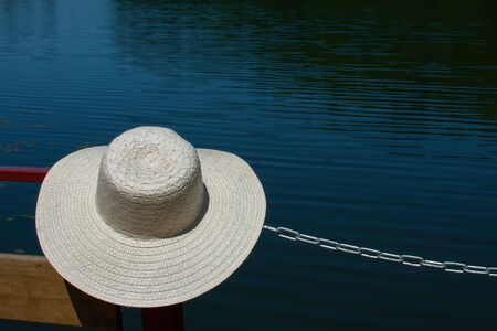 Summer holiday banner. Beach accessory-a straw hat, on a blue turquoise background of water. Vacation travel concept Standard-Bild