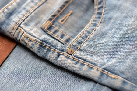Close-up of blue denim texture. Denim jeans background, space to copy your design or text. Фото со стока