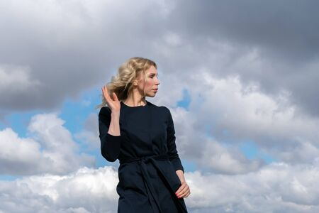 Portrait of a middle-aged blonde in a summer black coat against a cloudy sky. Copy space for your text or design.