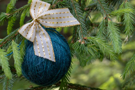 Christmas background with balls of yarn. Blue wool ball hanging on the green branches of a Christmas tree. Horizontal poster with copy space. The concept of a winter gift, present for handwork