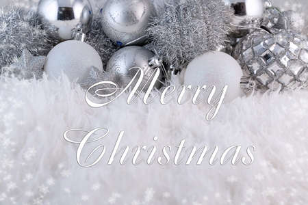merry christmas greeting text on shiny silver christmas tree decorations background