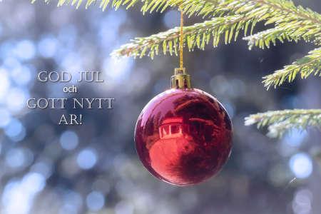 God Jul och Gott Nytt Ar means Merry Christmas and Happy New Year in Swedish, Danish and Norwegian. Red Christmas ball hanging on Christmas tree.