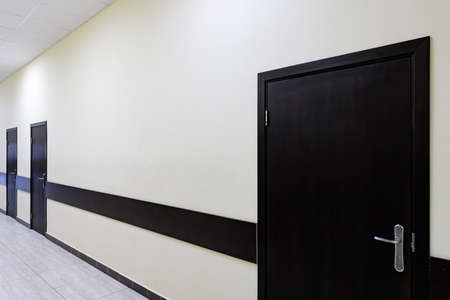 empty corridor in the modern office building. There are many brown doors along a very long corridor with beige walls.