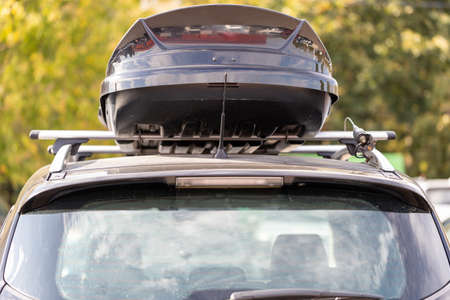 Assembled and closed, roomy roof rack or roof box for the safety of things against a blurred background of green leaves. Back view. A family vacation trip