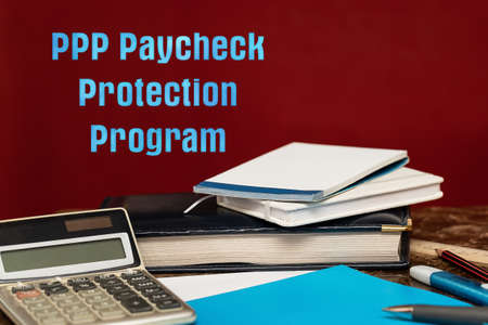 PPP Loan Paycheck Protection Program. Blue letters on a red background. Financial instruments concept.