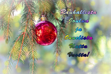 The greeting text in Finnish means Peaceful Christmas and Happy New Year. Blurred background of a Christmas tree decorated with toy red ball. Imagens