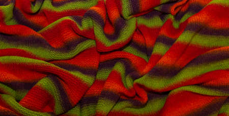 Large handmade merino wool blanket, super chunky yarn, fashion concept. Close-up of a knitted designer blanket in red, green and brown wool. Selective focus Imagens
