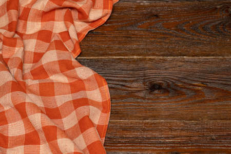 Checkered linen tablecloth on a wooden background. Brown wooden table. Selective focus. Copy space. Place for food and drink. Picnic and thanksgiving day concept. Restaurant, menu Reklamní fotografie