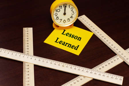 Message LESSON LEARNED on a yellow sticky note next to a yellow clock and wooden rulers against the background of the table. Education concept